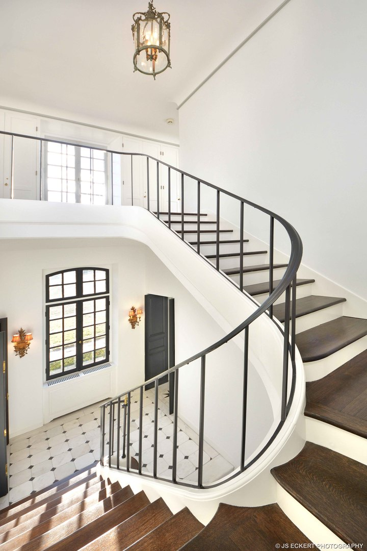 Beautiful renovated modern French grand staircase with wrought iron railings, and stained wood steps. La Lanterne by David Adler in Lake Bluff, IL.