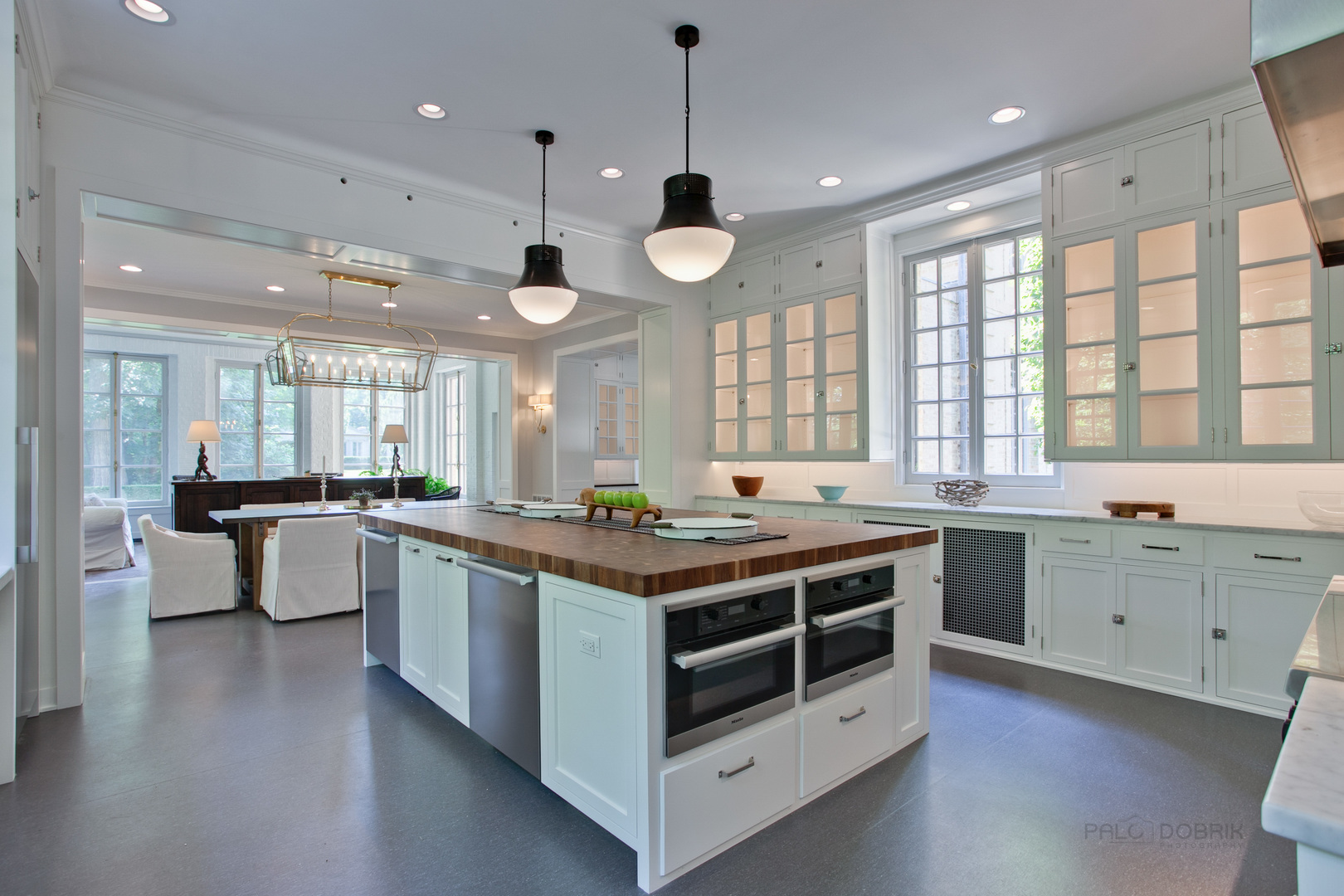 Beautiful classic white kitchen with butcher block center island in a French chateau by David Adler known as the Carolyn More Ely House. Come see the tour of this amazing historic home for sale.