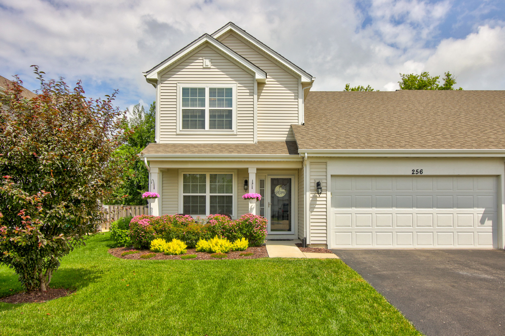 This Sharp Lily Model Duplex is Ready for You! Beautiful Professionally Landscaped Front Porch Area!